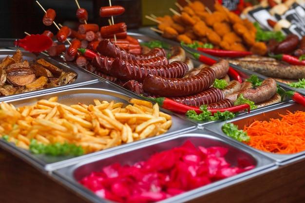 Vários alimentos na feira anual de natal. salsichas fritas, batatas fritas e outros alimentos saborosos