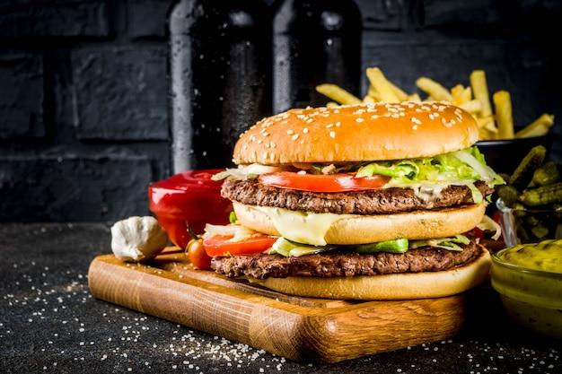 Vários alimentos para festas, hambúrgueres, batatas fritas, batatas fritas, pepinos em conserva, cebola, tomate e garrafas de cerveja gelada