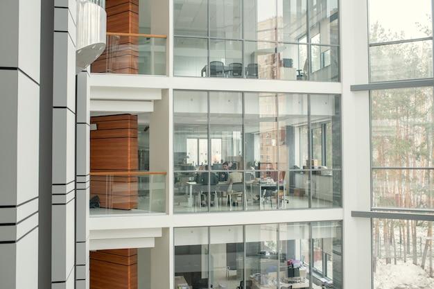 Vários andares com salas de escritório envidraçadas e paredes de madeira nos corredores do moderno centro de negócios, pessoas trabalhando no escritório