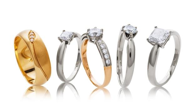 Vários anéis de casamento de ouro com diamantes isolados no branco