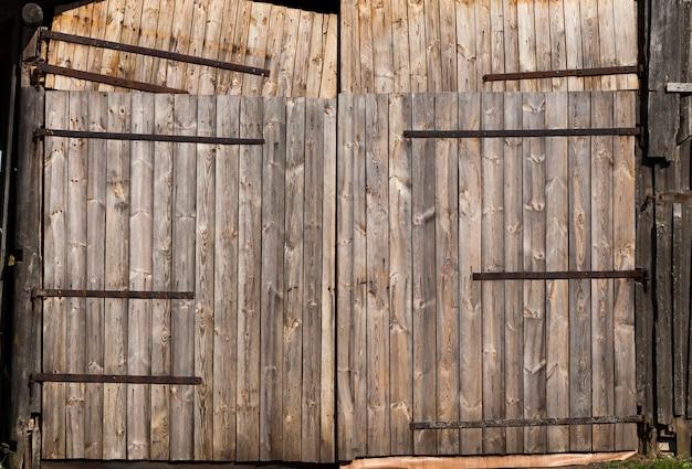 Vários antigos portões de madeira em um celeiro no campo, close-up de um antigo prédio rústico