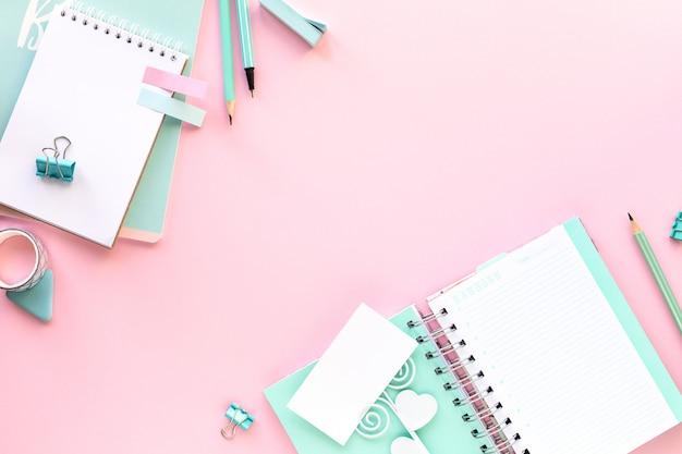 Vários artigos de papelaria coloridos para escola e escritório em fundo rosa com copyspace.