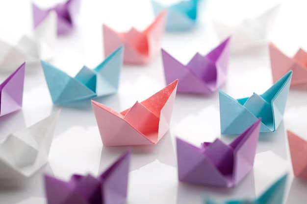 Vários barcos de papel colorido sobre fundo branco.