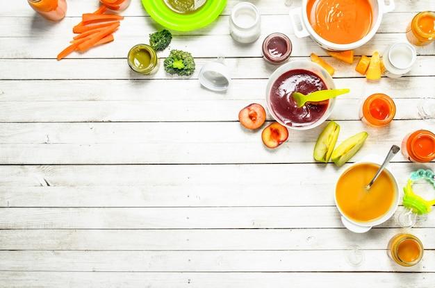 Vários bebês purês de frutas e vegetais frescos.