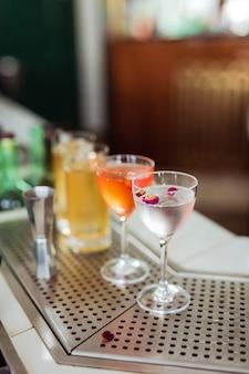 Vários belos coquetéis em nick e nora e copos altos no bar