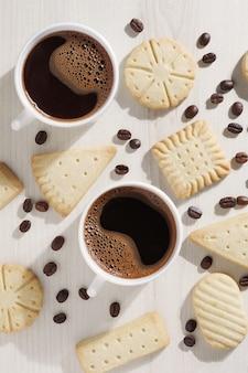 Vários biscoitos amanteigados e duas xícaras de café na vista de cima da mesa