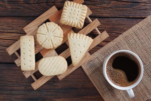 Vários biscoitos amanteigados e uma xícara de café na vista de cima de uma mesa de madeira rústica