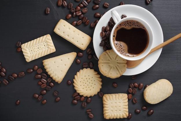 Vários biscoitos amanteigados e uma xícara de café na vista superior da mesa de madeira preta