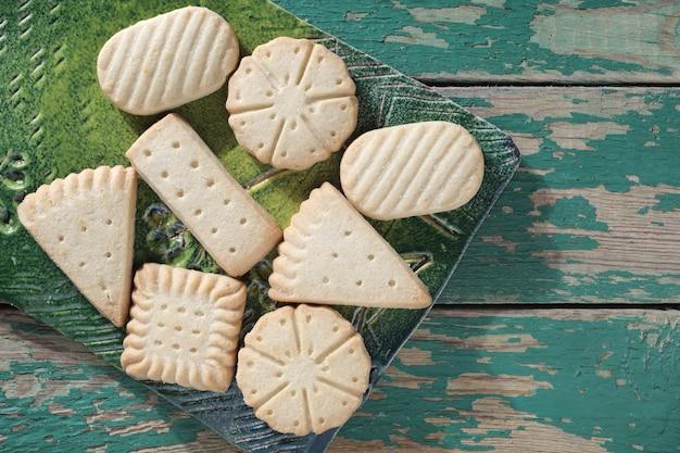 Vários biscoitos amanteigados em uma placa de cerâmica na vista superior do antigo fundo de madeira verde