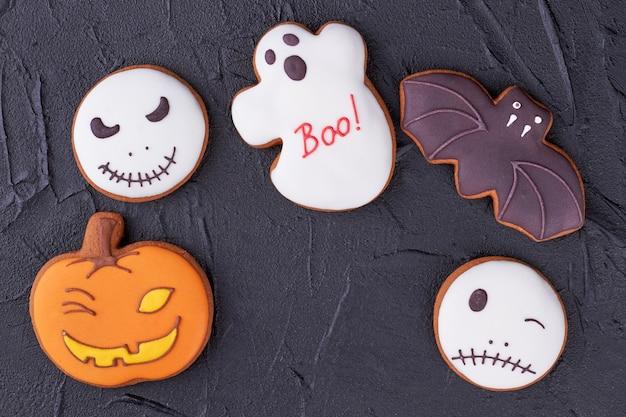 Vários biscoitos de halloween em fundo preto.