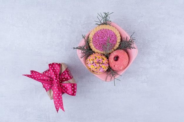 Vários biscoitos decorados com sprinklers e caixa de presente.