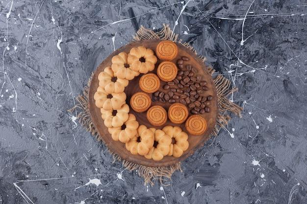 Vários biscoitos doces com grãos de café de aroma em uma peça de madeira.