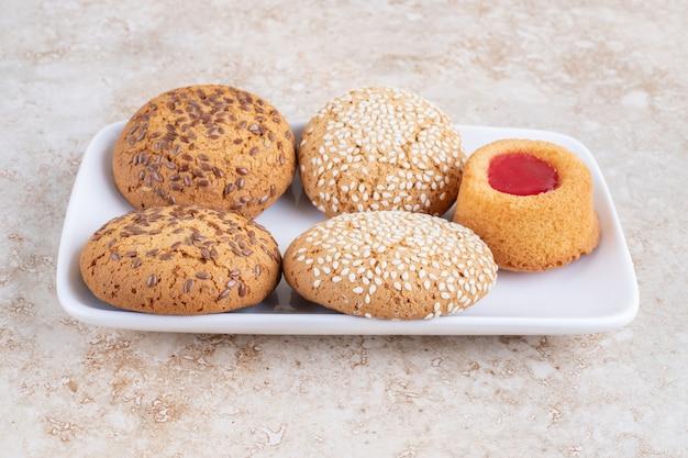 Vários biscoitos e amendoim descascado num prato, na mesa de mármore.