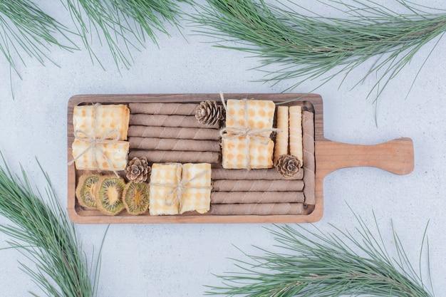Vários biscoitos e fatias de kiwi secas na placa de madeira.