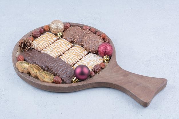 Vários biscoitos, frutas secas e bolas de natal na placa de madeira.
