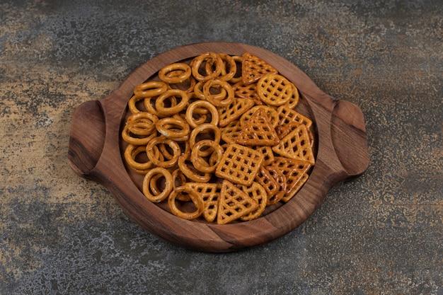 Vários biscoitos salgados na placa de madeira.