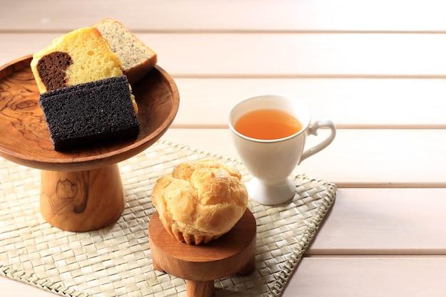 Vários bolo de fatia para caixa de lanche da indonésia. choux, bolo de banana, bolo de mármore e bolo de arroz pegajoso preto. servido com chá. copie o espaço no fundo de madeira