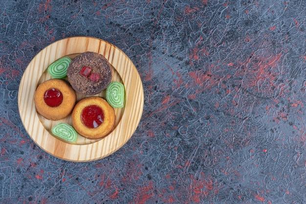 Vários bolos e geleias em uma bandeja de madeira na mesa abstrata.