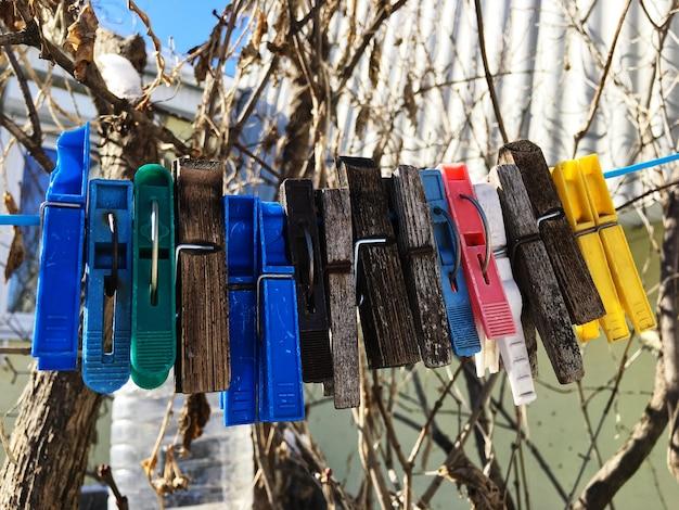 Vários cabides de madeira de plástico multicoloridos pendurados em um fio no quintal