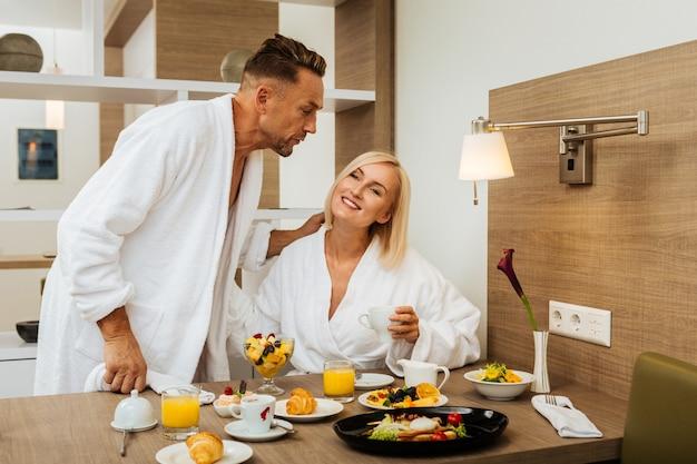 Vários cafés da manhã. casal feliz com vestes brancas de hotel tomando café da manhã romântico e curtindo a vida
