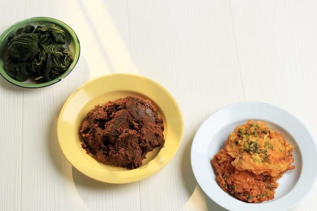 Vários caseiros masakan padang ou minang cuisine em fundo branco com espaço de cópia. popular como nasi padang.