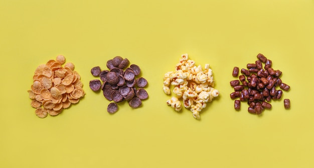 Vários cereais cornflakes snack e pipoca pilha na vista superior amarela para café da manhã