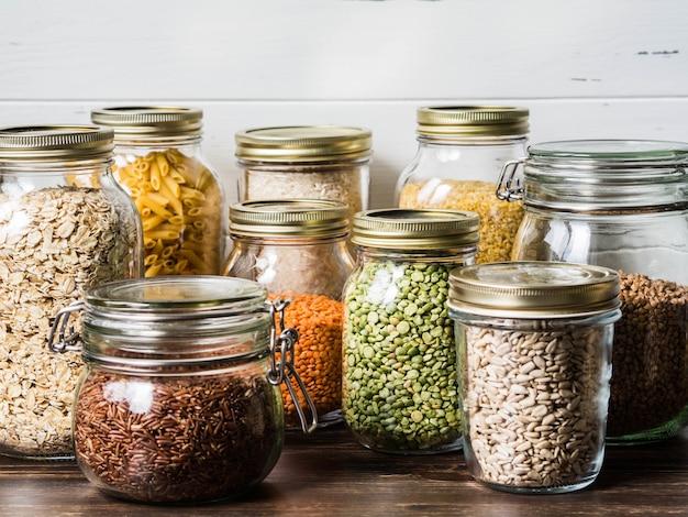 Vários cereais e sementes em frascos de vidro em cima da mesa na cozinha