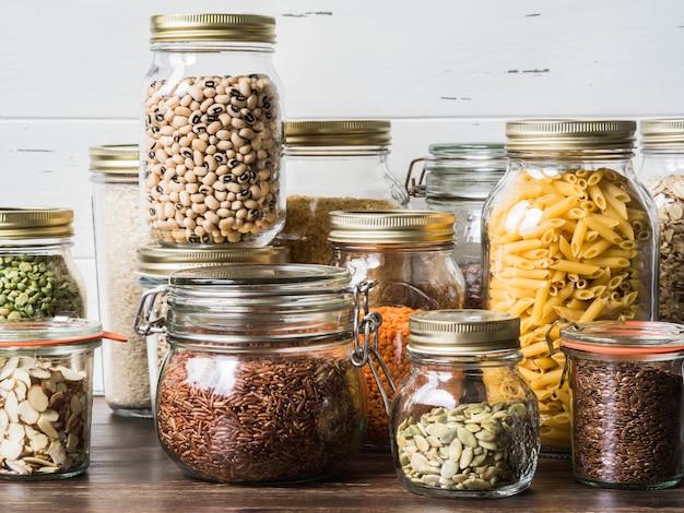 Vários cereais e sementes em potes de vidro sobre a mesa na cozinha