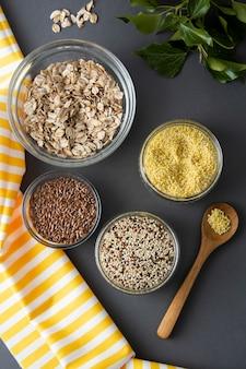 Vários cereais não cozidos. tipos diferentes de aveia em flocos em umas bacias no fundo cinzento.