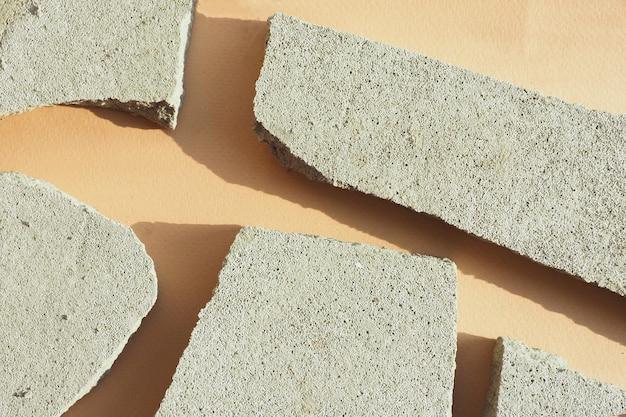 Vários chips de concreto em um fundo de papel bege em luz forte com sombras. layout plano, vista superior.