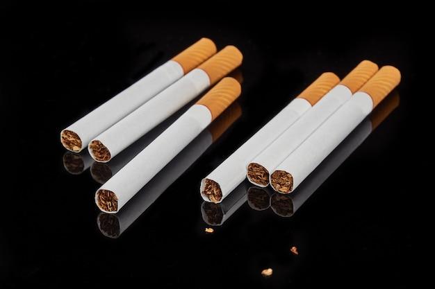Vários cigarros de filtro em uma superfície preta brilhante