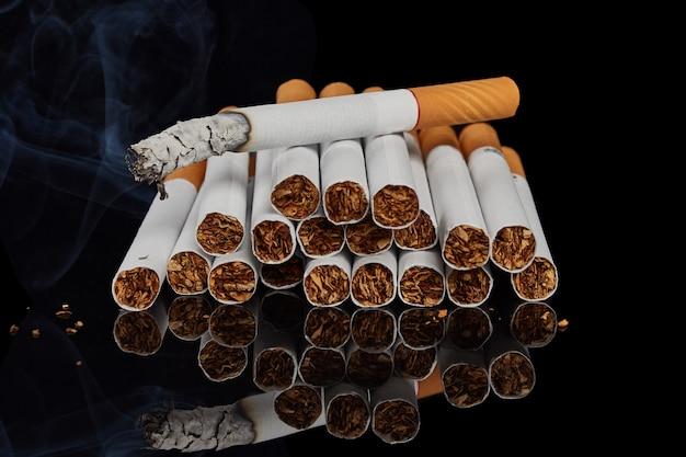 Vários cigarros inteiros e um cigarro fumegante em uma superfície preta