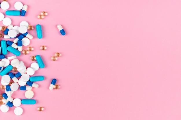 Vários comprimidos brancos e azuis em fundo rosa