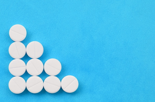 Vários comprimidos brancos mentem sobre um fundo azul brilhante sob a forma de uma seta triangular