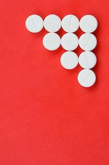 Vários comprimidos brancos mentem sobre um fundo vermelho brilhante sob a forma de uma seta triangular
