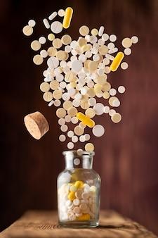 Vários comprimidos voam de um frasco de vidro sobre uma superfície de madeira