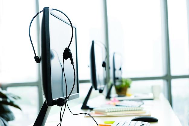 Vários computadores estão sobre a mesa com fones de ouvido dos funcionários