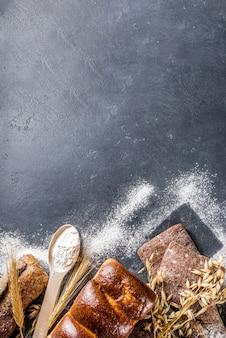 Vários conjuntos de pão. muitos pães de trigo, grãos e centeio diferentes com espigas de centeio e trigo, farinha e ferramentas de padeiro em um fundo branco de madeira