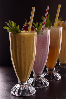 Vários copos com batatas fritas refrescantes com banana, morango e mamão, com gelo com tubo de coquetel em fundo preto