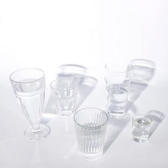 Vários copos de água com sombra no fundo branco