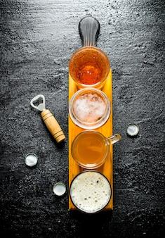 Vários copos de cerveja em uma tábua de madeira com abridor. na mesa rústica preta