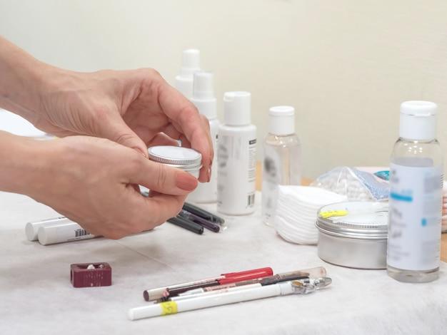 Vários cremes e produtos para colorir sobrancelhas estão sobre a mesa no salão de beleza, foco suave.