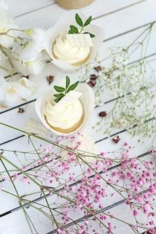 Vários cupcakes e muffins com creme de manteiga branca e uma rosa rosa viva em uma mesa de madeira branca.