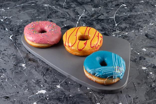 Vários deliciosos donuts com glacê cremoso na mesa de mármore.