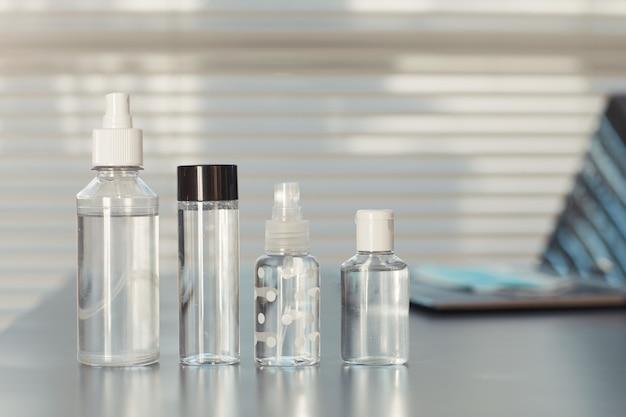 Vários desinfetantes para as mãos na mesa vazia do local de trabalho em um escritório pós-pandêmico