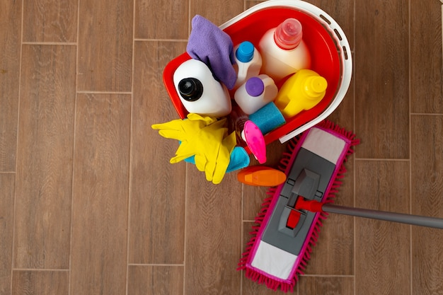 Vários detergentes de limpeza doméstica e garrafas em um balde de plástico no chão. conceito de limpeza