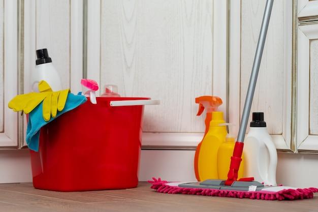 Vários detergentes de limpeza doméstica e garrafas em um balde de plástico no chão