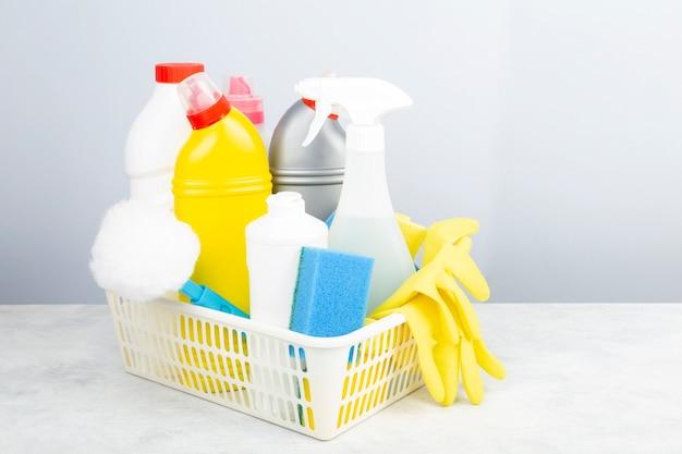 Vários detergentes e agentes de limpeza, esponjas, guardanapos e luvas de borracha, fundo cinza. copie o espaço