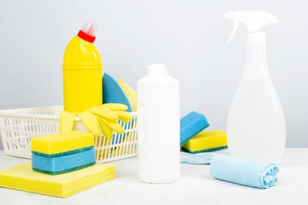 Vários detergentes e agentes de limpeza, esponjas, guardanapos e luvas de borracha, fundo cinza