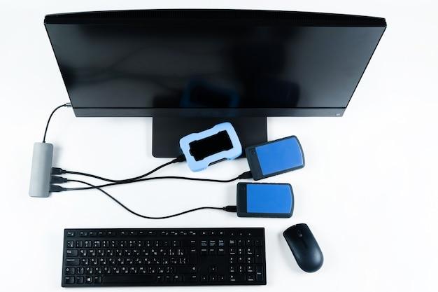 Vários discos rígidos externos conectados a um monobloco em um fundo branco. computador com disco rígido.